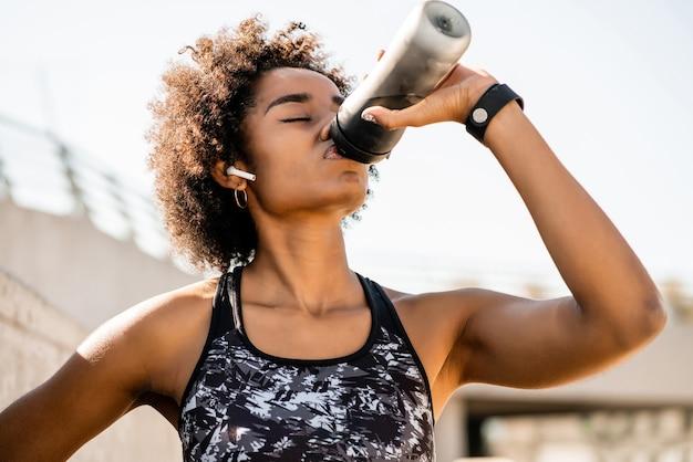 Retrato de mulher atleta afro bebendo água após malhar ao ar livre