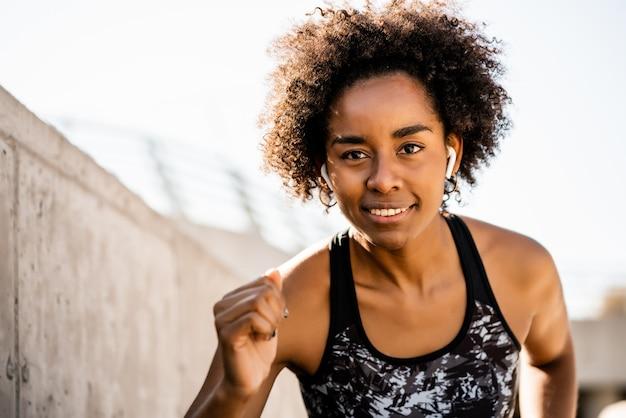 Retrato de mulher atleta afro correndo e fazendo exercício ao ar livre. esporte e estilo de vida saudável.