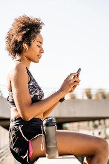Retrato de mulher atleta afro usando seu telefone celular e relaxando depois de malhar ao ar livre