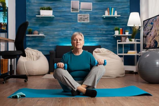 Retrato de mulher atleta sênior olhando para a câmera, sentado em posição de lótus no tapete de ioga na sala de estar durante um treino de bem-estar