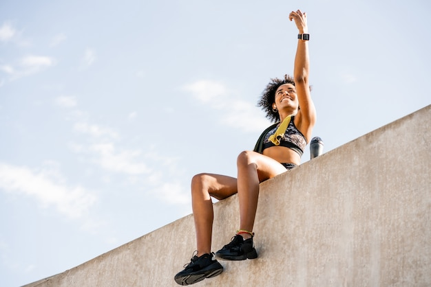 Retrato de mulher atleta tomando uma selfie com seu telefone celular e relaxando depois do treino ao ar livre.