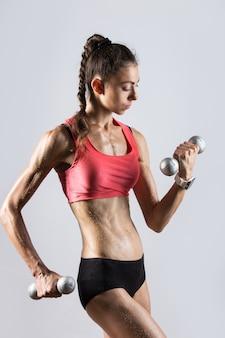 Retrato de mulher atlética bonita suando ao levantar dumbbells