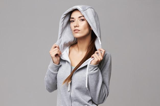 Retrato de mulher atlética brutal na capa e sportswear em branco.