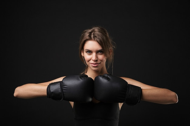 Retrato de mulher atlética caucasiana em roupas esportivas, posando para a câmera com luvas de boxe durante treino no ginásio isolado sobre fundo preto