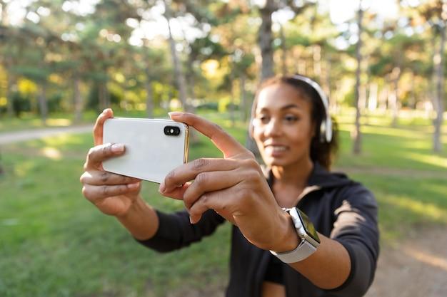 Retrato de mulher atlética de 20 anos, vestindo um agasalho esportivo preto e fones de ouvido, tirando uma foto de selfie no celular enquanto caminha pelo parque verde