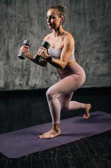 Retrato de mulher atlética jovem musculoso com corpo lindo perfeito vestindo roupas esportivas, fazendo agachamento usando halteres. mulher caucasiana de aptidão posando em estúdio com fundo cinza escuro.