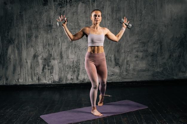 Retrato de mulher atlética jovem musculoso com corpo lindo perfeito vestindo roupas esportivas, levantando os braços segurando halteres. mulher caucasiana de aptidão posando em estúdio com fundo cinza escuro.