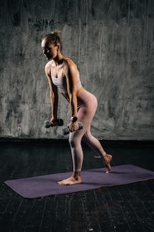 Retrato de mulher atlética jovem musculoso com corpo lindo perfeito vestindo roupas esportivas, praticando estocadas usando halteres. mulher caucasiana de aptidão posando em estúdio com fundo cinza escuro.