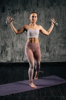 Retrato de mulher atlética jovem musculoso vestindo roupas esportivas, levantando os braços segurando halteres.