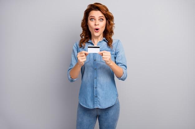 Retrato de mulher atônita segurando cartão de crédito impressionada com banco on-line sistema de pagamento fácil grite uau omg use roupas estilo boa aparência isoladas sobre parede de cor cinza