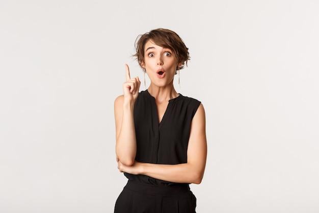 Retrato de mulher atraente animada com roupa formal, levantando o dedo em gesto de eureka, tenho uma ideia, branco.