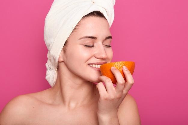 Retrato de mulher atraente detém laranja, desfrutando de cheiro fresco de frutas, encantadora garota vestindo toalha e ombros nus