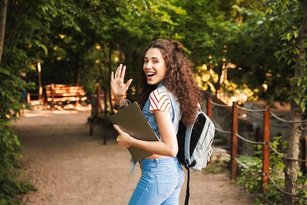 Retrato de mulher atraente e amigável usando uma mochila, acenando com a mão enquanto caminha pelo parque verde com um laptop prateado nas mãos