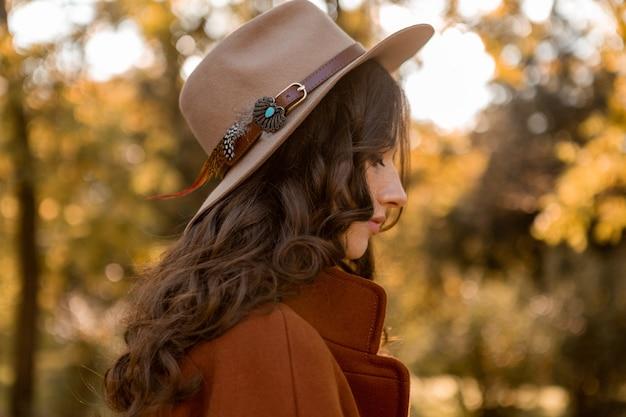 Retrato de mulher atraente e elegante com cabelo longo encaracolado caminhando no parque vestida com casaco marrom quente outono na moda, estilo de rua usando chapéu