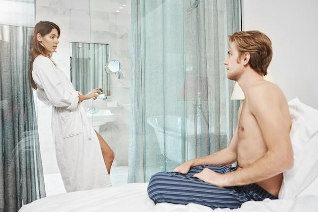Retrato de mulher atraente europeia em roupão de hotel em pé na porta, olhando para o namorado que se senta na cama com olhar apaixonado. casal apaixonado de férias raramente sai do quarto