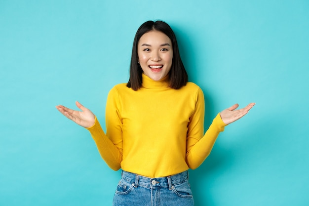 Retrato de mulher atraente feliz espalhou as mãos para os lados e sorrindo, surpreso ao ver você, em pé sobre um fundo azul.