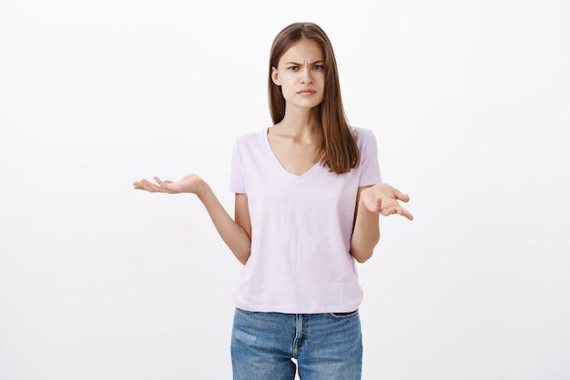 Retrato de mulher atraente, insatisfeita, confusa e perplexa em traje casual, encolhendo os ombros com as mãos abertas e expressão perplexa franzindo a testa por ser um ignorante