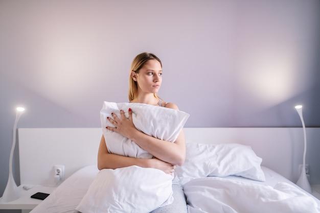 Retrato de mulher atraente triste sentado na cama no quarto e abraçando o travesseiro