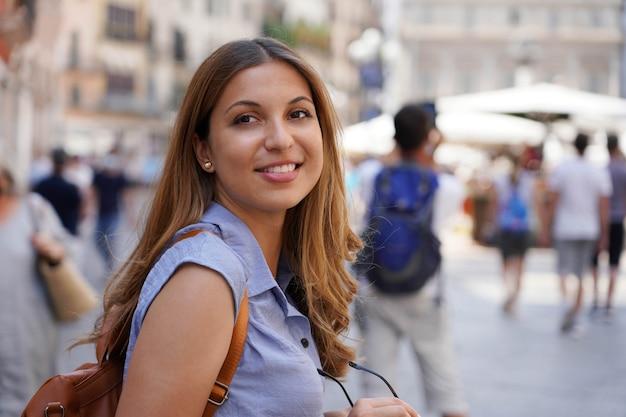 Retrato de mulher atraente turista olhando para trás com pessoas desfocadas no fundo. copie o espaço.