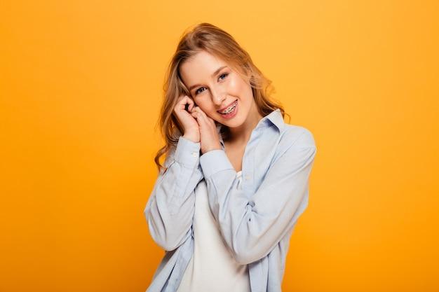 Retrato de mulher atraente usando aparelho posando na câmera com olhar sedutor sincero, isolado sobre fundo amarelo