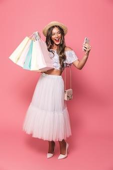 Retrato de mulher atraente usando chapéu de palha e saia fofa segurando pacotes de compras de papel colorido e tomando selfie no smartphone