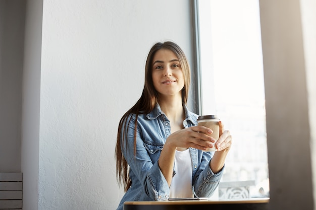 Retrato de mulher bonita alegre com cabelos escuros e roupas elegantes, sentado na cafeteria, sorrindo, bebendo café e. conceito de estilo de vida.