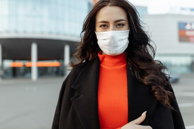 Retrato de mulher bonita andando na rua usando máscara protetora como proteção contra doenças infecciosas. modelo infeliz atrativo com gripe ao ar livre