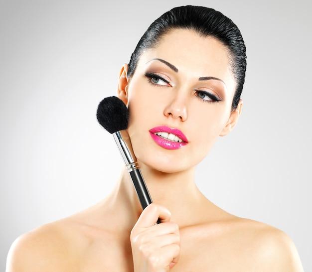 Retrato de mulher bonita aplicando blush no rosto com escova cosmética