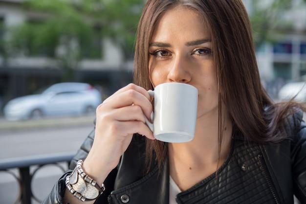 Retrato de mulher bonita caucasiana, bebendo café em um terraço na rua.