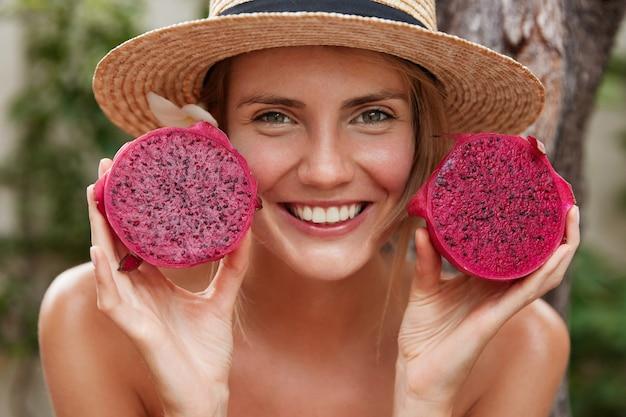 Retrato de mulher bonita com aparência atraente, usa chapéu de palha de verão e segura a fruta do dragão