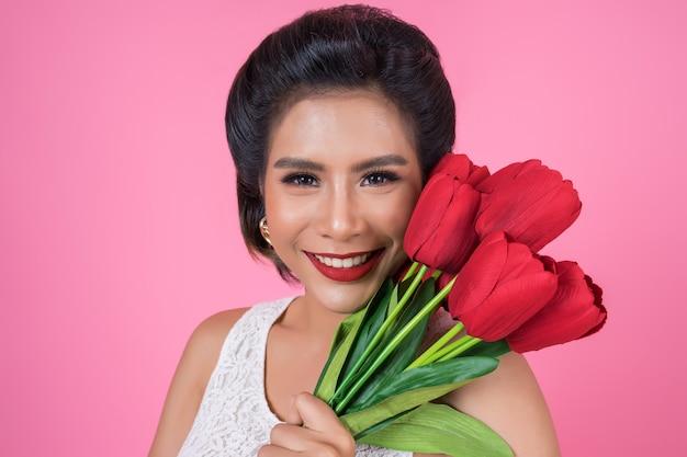 Retrato de mulher bonita com buquê de flores tulipa vermelha