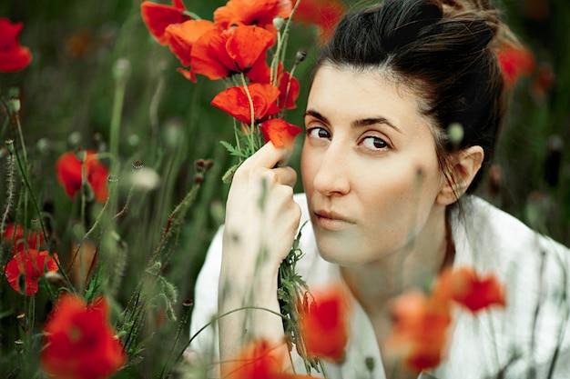 Retrato de mulher bonita com o buquê de flores de papoulas