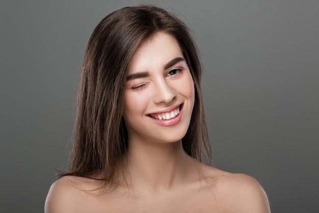 Retrato de mulher bonita com pele perfeita e maquiagem natural piscando no fundo cinza
