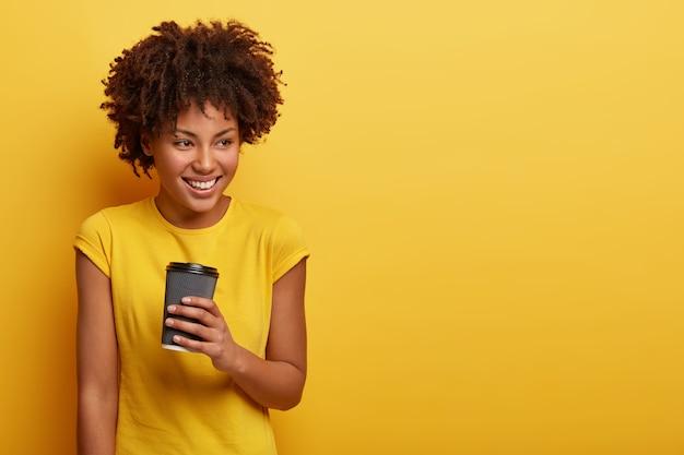 Retrato de mulher bonita com penteado encaracolado, com expressão facial satisfeita e pensativa, gosta de café aromático quente, usa camiseta amarela