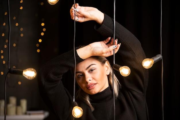 Retrato de mulher bonita com suéter preto em pé e posando