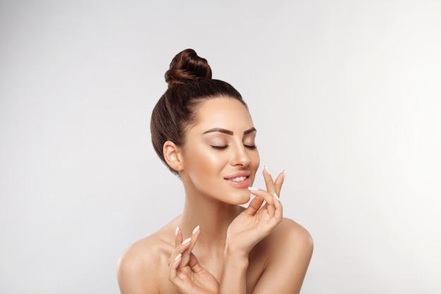 Retrato de mulher bonita, conceito de cuidados com a pele, cuidados com a pele. dermatologia. retrato de mãos femininas com unhas de manicure tocando seu rosto.