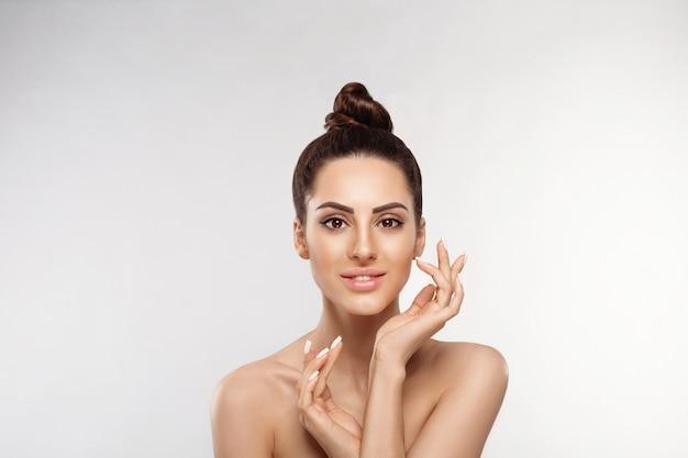 Retrato de mulher bonita, conceito de cuidados com a pele, pele bonita. retrato de mãos femininas com unhas de manicure. cosméticos femininos. tratamento facial