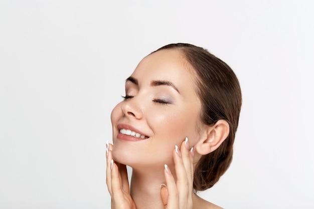 Retrato de mulher bonita, conceito de cuidados com a pele, pele bonita. retrato de mãos femininas com unhas de manicure. cosméticos para meninas. tratamento facial.