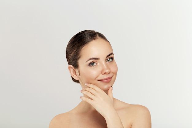 Retrato de mulher bonita, conceito de cuidados com a pele, pele bonita. retrato de mãos femininas com unhas de manicure.