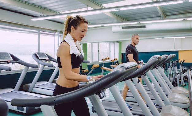 Retrato de mulher bonita, configuração do painel de controle da esteira para treinamento no centro de fitness. conceito de esporte e tecnologia.