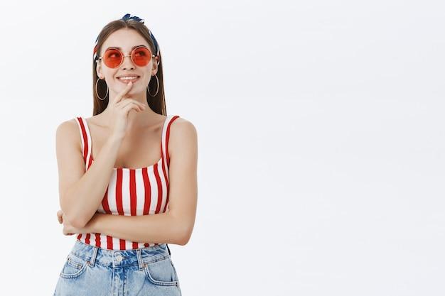 Retrato de mulher bonita, criativa, feliz e pensativa, de óculos escuros e blusa listrada tocando o lábio olhando para cima enquanto toma uma decisão contra a parede cinza