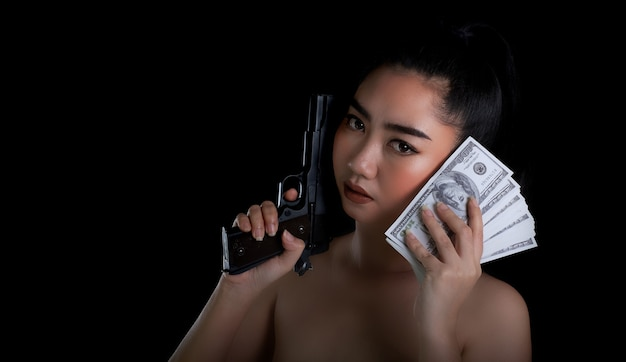 Retrato de mulher bonita da ásia com uma mão segurando uma arma e uma nota de dinheiro 100 dsd em fundo preto