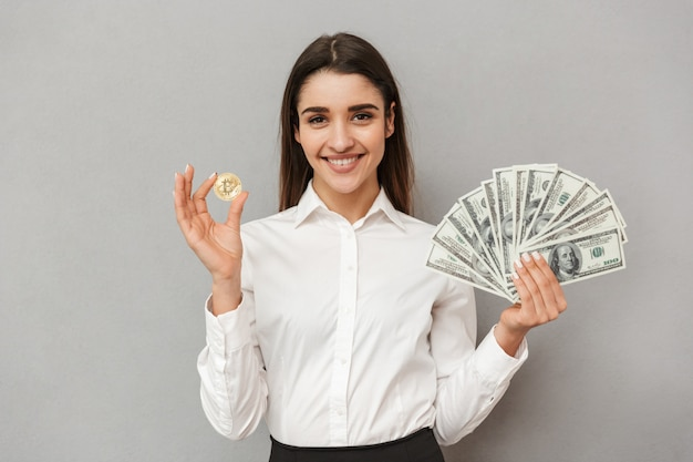 Retrato de mulher bonita de escritório com longos cabelos castanhos em roupas de trabalho mostrando bitcoin e muitas notas de dólar, isoladas sobre uma parede cinza
