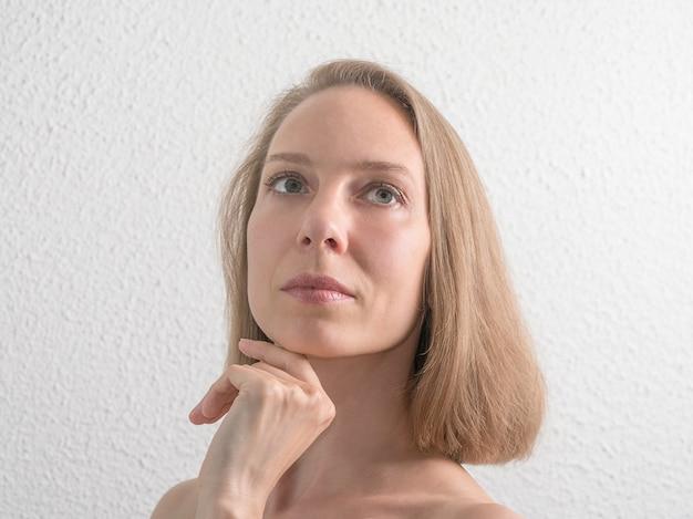 Retrato de mulher bonita de meia idade tocando seu rosto na parede branca