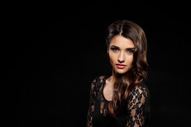 Retrato de mulher bonita de vestido preto sobre parede escura