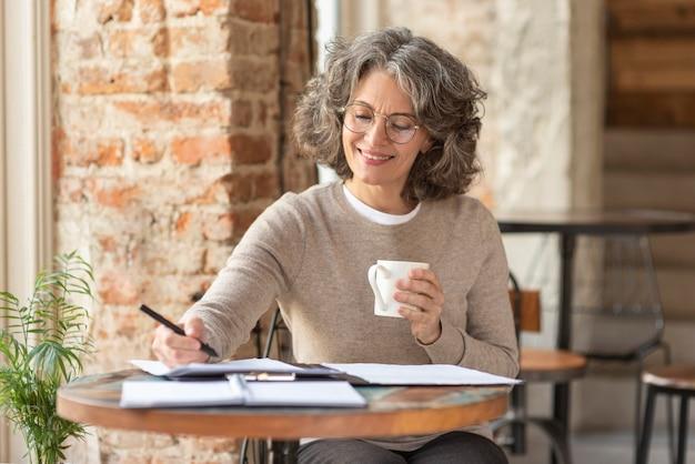 Retrato de mulher bonita desfrutando de uma xícara de café enquanto acorda