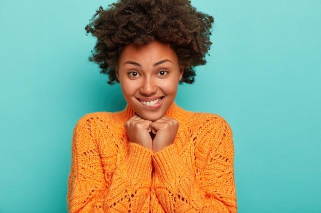 Retrato de mulher bonita e cacheada morde os lábios, mantém as mãos embaixo do queixo, olha com alegria e adoração, morde os lábios, sorrindo com os dentes, usa suéter de tricô, recebe notícias agradáveis, estande interior