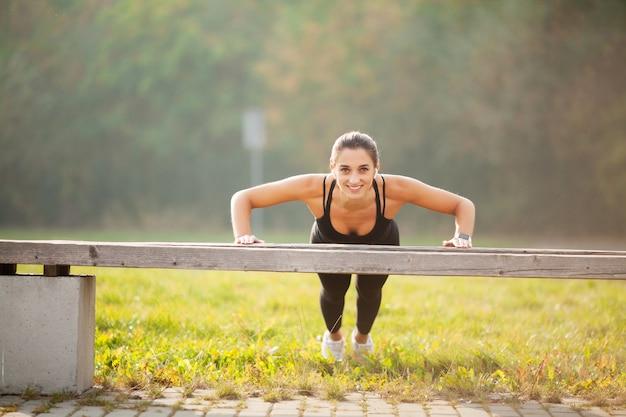 Retrato de mulher bonita e desportiva 20 anos no sportswear fazendo flexões e ouvindo música com fone de ouvido bluetooth durante treino no parque verde