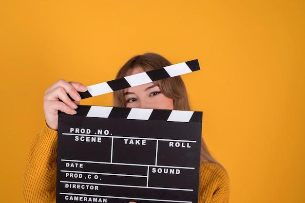 Retrato de mulher bonita e feliz sorrindo, com claquete, em fundo amarelo-laranja
