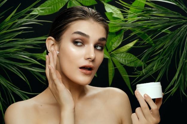 Retrato de mulher bonita em arbustos de palma, pele bonita do rosto
